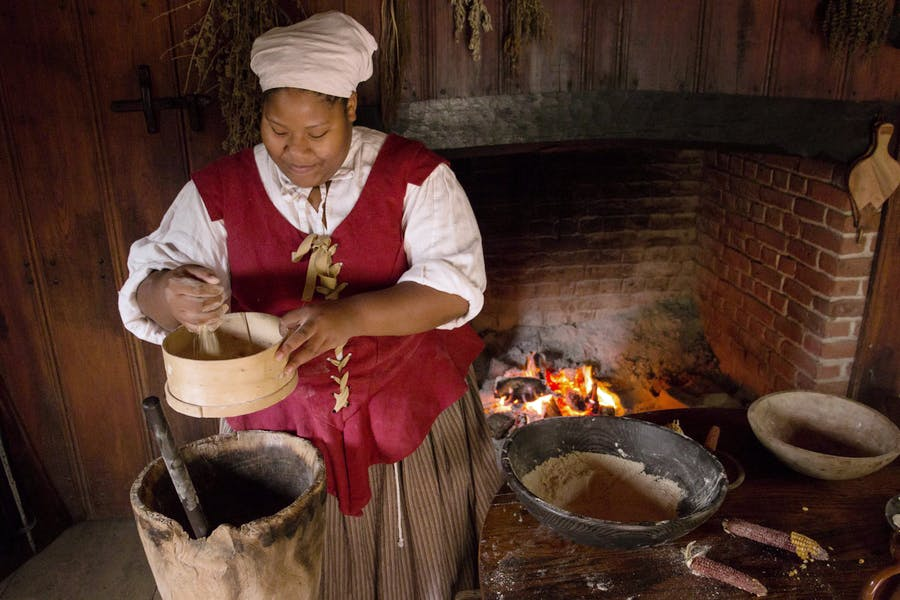 An indentured servant is preparing a meal in the main room of the hose at the Godiah Spray Tobacco Plantation