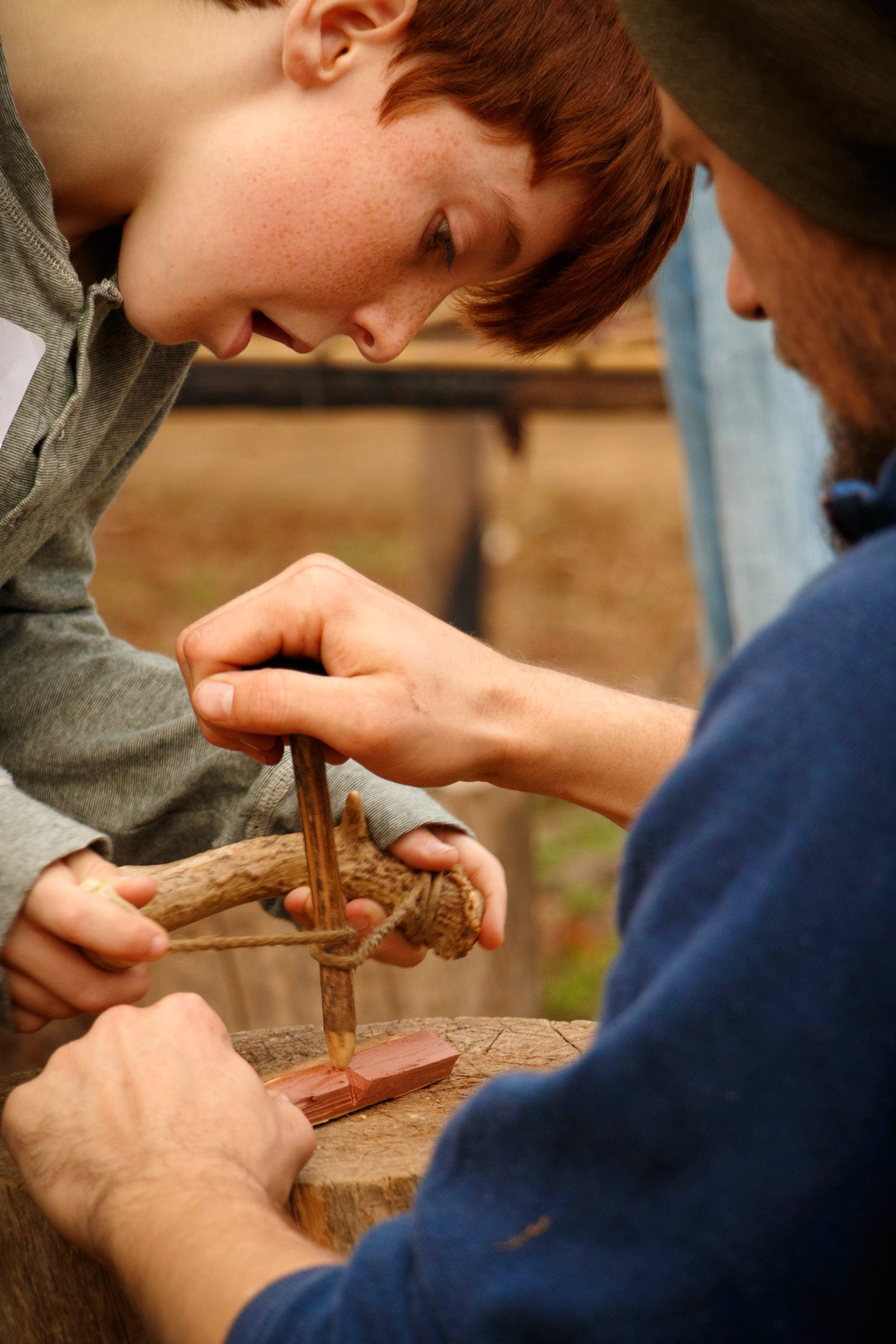 HSMC staff person teaches a young visitor how to start a fire with a bowdrill