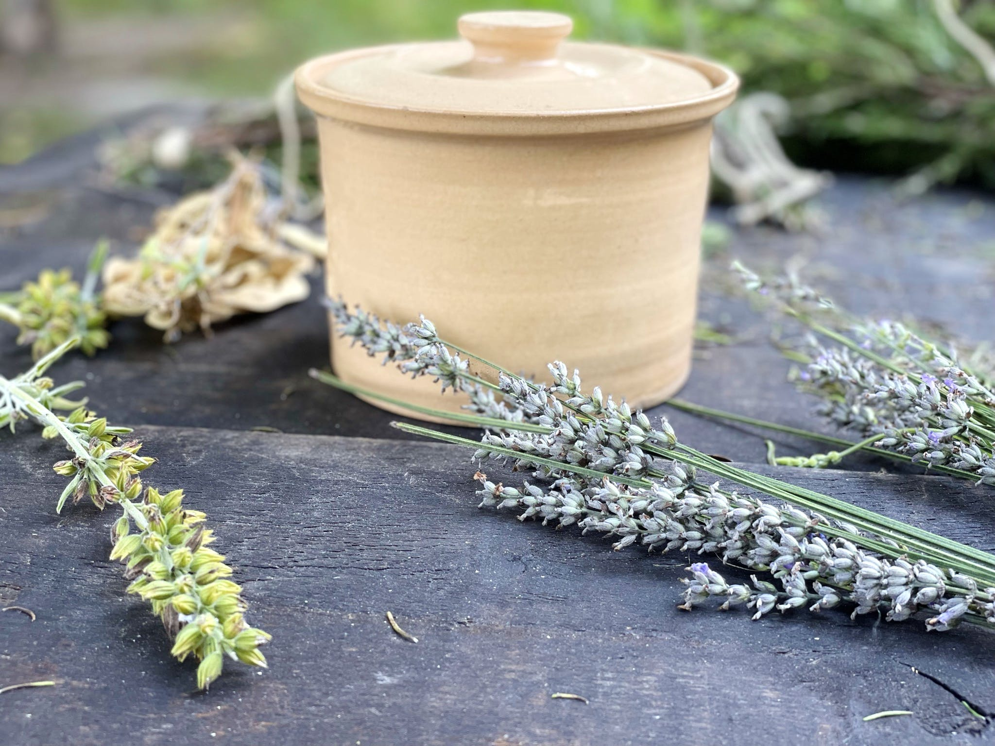 Fresh cut herbs are scattered on a wooden table