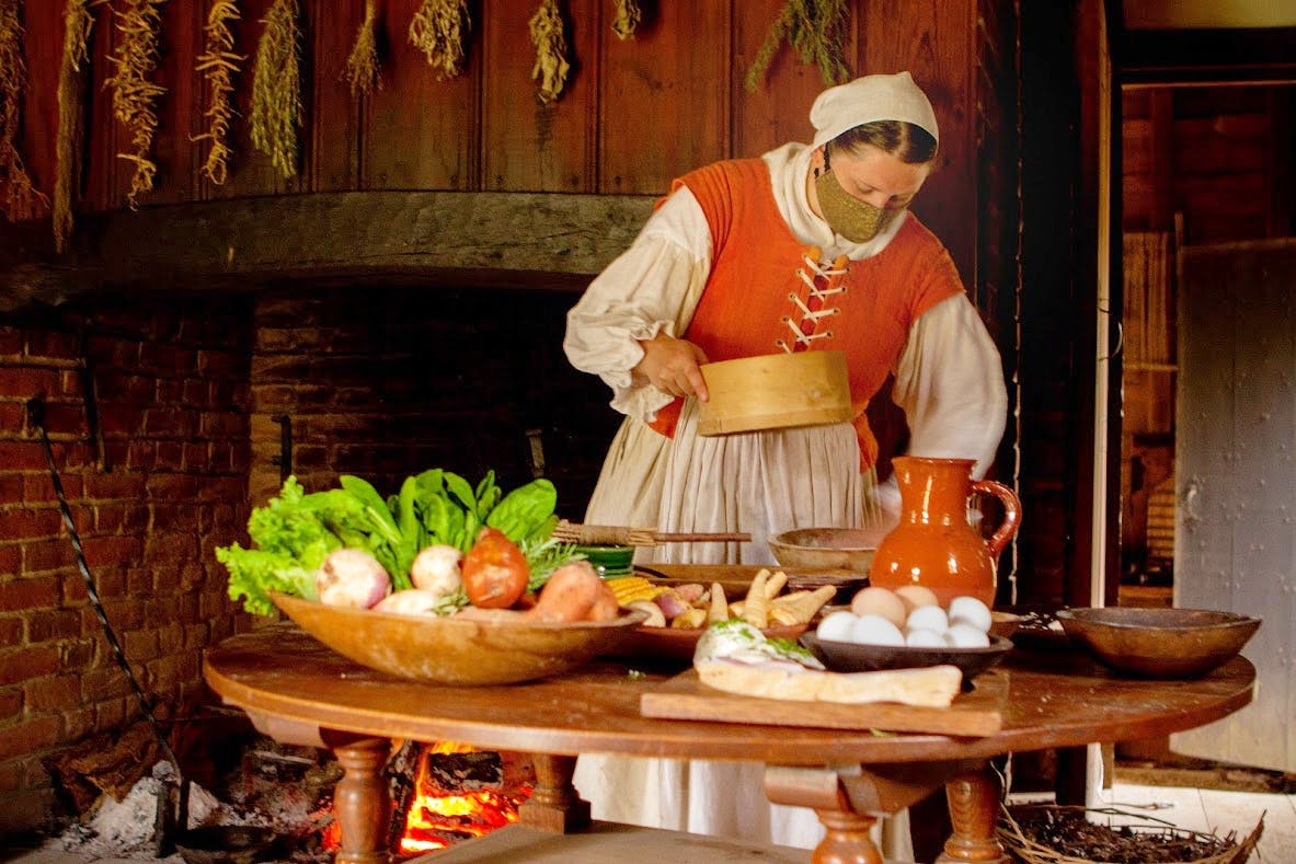 A woman in a 17th century costume is preparing food in front of a fire.