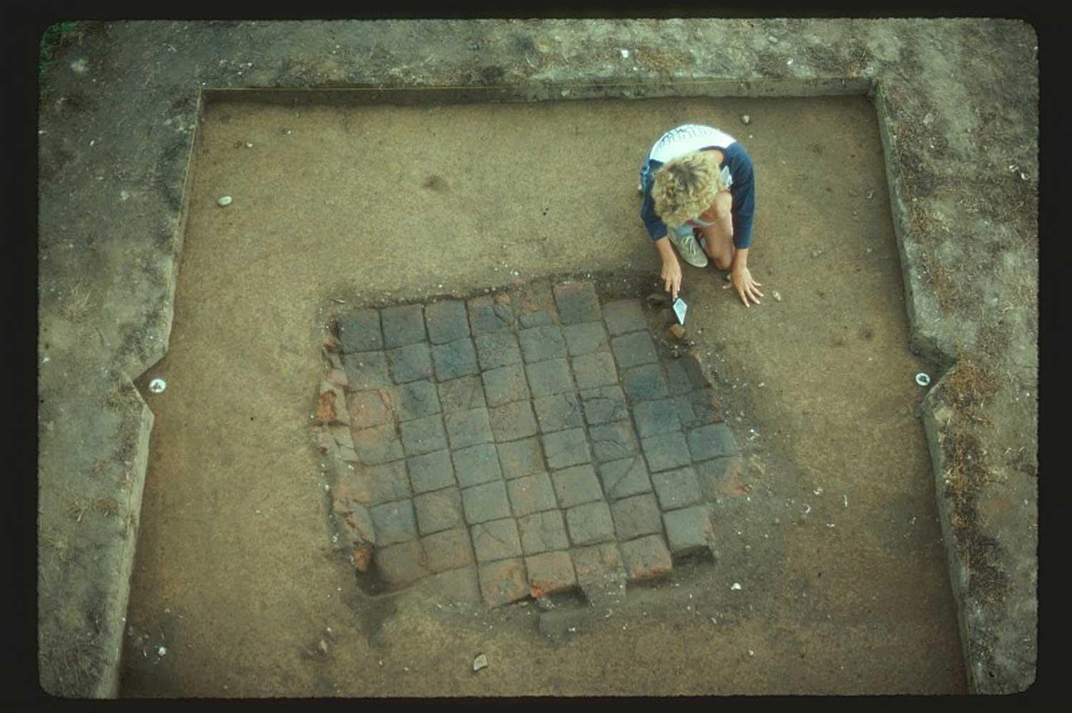 Part of Smith's Ordinary being uncovered (note the dark spots on the tiles from burning during the 1678 fire)